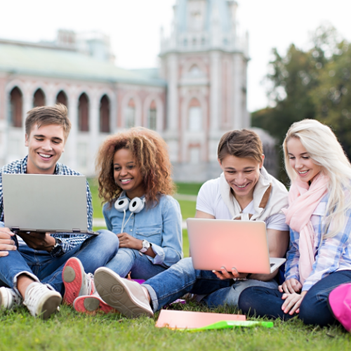 Group of four university students sitting on a lawn in front of a building