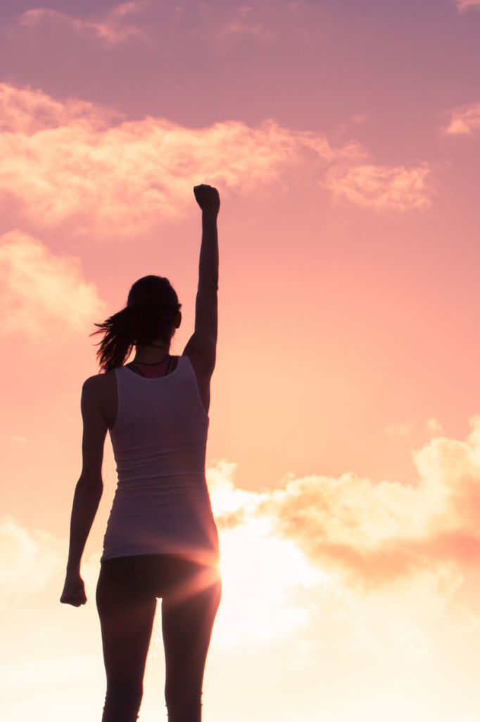woman holding arm up against the sky